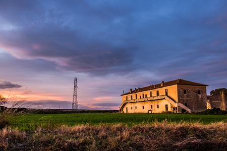 Old farmhouse at sunset Stock Photo
