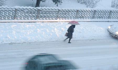 Girl walking in heavy snow - motion blur effect photo