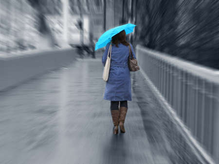 Girl walking in the rain with umbrella, dressed in a blue mac with an azure umbrella photo
