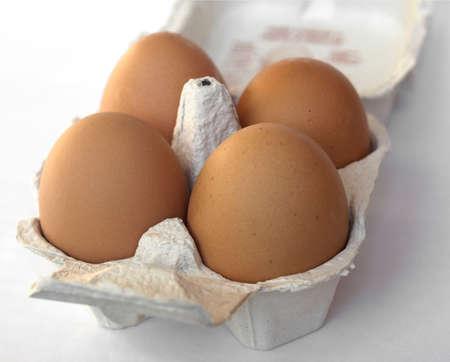 Four eggs in a cardboard wrap box