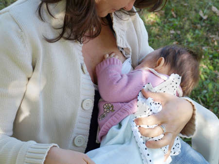 Pretty young brunette mum breastfeeding her baby Stock Photo