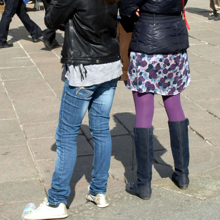 Fashionable girls in miniskirt and jeans, in a urban scene photo