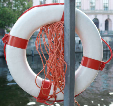 Life buoy on a river over blurred urban background photo
