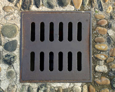 Detail of a manhole grid in the street photo