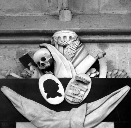 thou: Memento mori (Remember thou shalt die) - Ancient medieval sculpture with skull and reapers sickle in Koelner Dom cathedral, Koeln, Germany