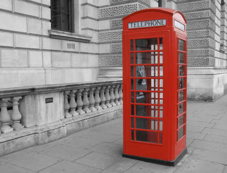 Traditional red telephone box in London, UK - selective black & white background