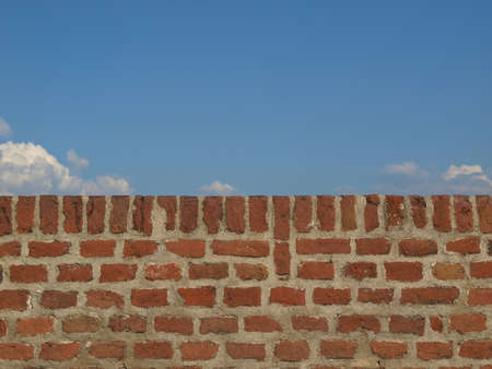 A wall with blue sky with clouds behind photo