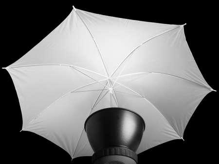 studio lighting: Lighting photo umbrella used with strobo lights in photographic studio - over black background Stock Photo