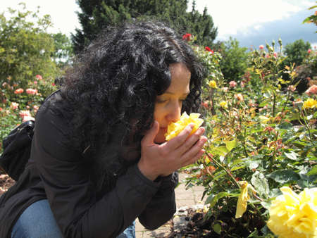 Pretty young brunette girl woman female smelling roses in the garden photo
