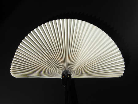 airflow: Hand held fan used to induce an airflow for cooling or refreshing oneself - over black background