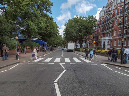 LONDON, ENGLAND, UK - JUNE 18: People crossing the Abbey Road zebra crossing made famous by the 1969 Beatles album cover on June 18, 2011 in London, England, UK 에디토리얼