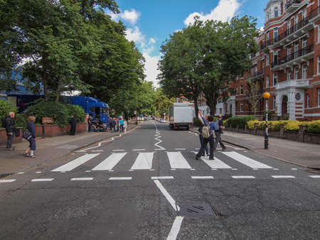 18: LONDON, ENGLAND, UK - JUNE 18: People crossing the Abbey Road zebra crossing made famous by the 1969 Beatles album cover on June 18, 2011 in London, England, UK Editorial