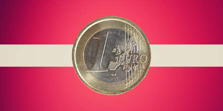 adopted: One Euro coin over the flag of Latvia, a country in the Baltic region of Northern Europe which adopted the Euro currency on January 1, 2014 Stock Photo