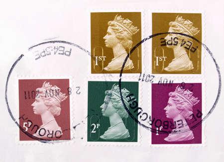 hm: LONDON, UK - DECEMBER 13, 2011: Range of British postage stamps with HM The Queen Elizabeth II