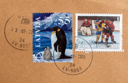 RIGA, LATVIA - FEBRUARY 21, 2014: Stamps printed by Latvian Posts showing penguins and hockey on ice players