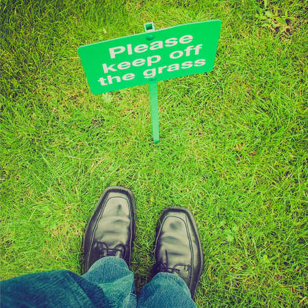 anti social: Vintage looking Keep off the grass sign in a meadow, with feet breaking the law Stock Photo