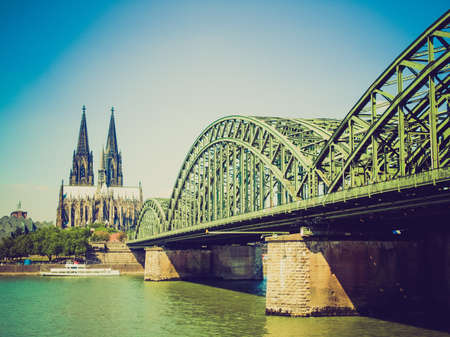 Vintage looking Koeln (Germany) panorama including the gothic cathedral and steel bridge over river Rhine photo