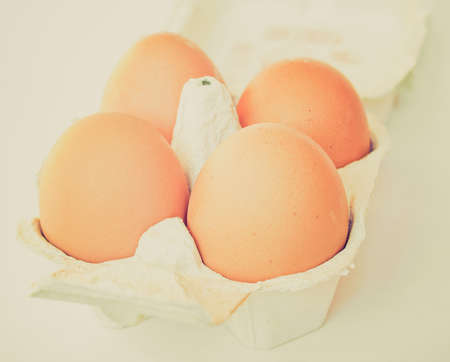 Vintage looking Four eggs in a cardboard wrap box Imagens