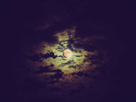 Vintage looking Dark baroque sky with full moon and clouds photo