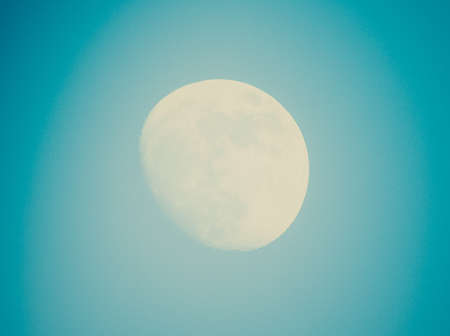 Vintage looking Full moon over a blue sky photo