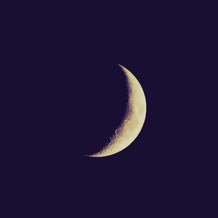 Vintage looking Crescent moon over black sky at night photo