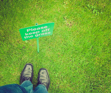 law breaking: Vintage looking Keep off the grass sign in a meadow, with feet breaking the law Stock Photo