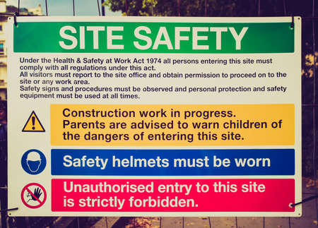 Vintage looking Safety sign in a construction site with work in progress photo