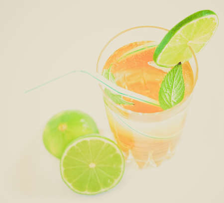 Vintage looking Cocktail mixed alcoholic drink with lime and peppermint photo