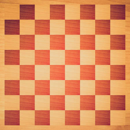 Vintage looking Wooden chessboard with light and dark wood checkers photo