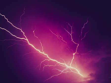 Vintage looking Bright lightning bolt over dark violet sky