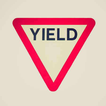 Vintage looking Give way or yield traffic sign isolated photo