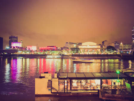 Vintage looking River Thames South Bank in London UK - at night