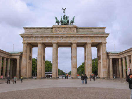 linking: BERLIN, GERMANY - MAY 11, 2014: Tourists visiting the Brandenburger Tor (Brandenburg Gate) linking East and West Berlin Editorial