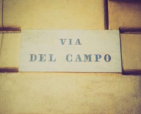 known: Vintage looking Tourists visiting Via del Campo street made famous by Italian musician Fabrizio de Andre in a well known song