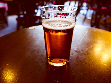 Vintage looking pint of English bitter ale in a pub