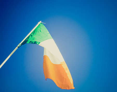 Vintage retro looking Irish flag over a blue sky background photo