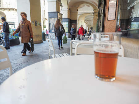 british people: TURIN, ITALY - OCTOBER 22, 2014: Pint of British ale on a pub table - selective focus on people