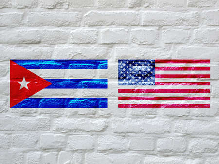 cuban flag: Flag of the USA and Cuba on a white bricks wall