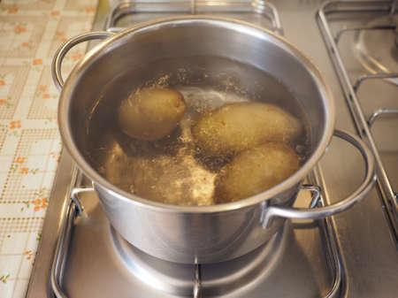 gas cooker: Hervir las patatas en una cacerola en una cocina de gas