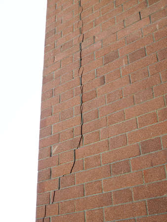 settling: Crack in a brick wall caused by excessive settling due to bad foundations or too much load or earthquake Stock Photo