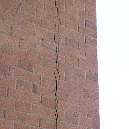 earthquake crack: Crack in a brick wall caused by excessive settling due to bad foundations or too much load or earthquake Stock Photo