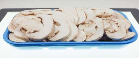 champignons: Agaricus bisporus aka champignons mushrooms in a tub on a table Stock Photo