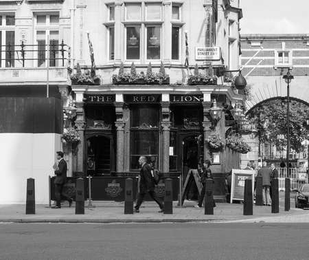elite: LONDON, UK - JUNE 09, 2015: The Red Lion pub situated in London political heart near the Houses of Parliament has been the favoured pub of the political elite for centuries in black and white Editorial