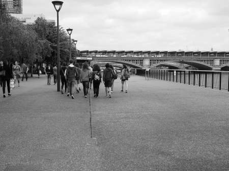 southbank: LONDON, UK - JUNE 10, 2015: People walking on the River Thames South Bank in black and white Editorial