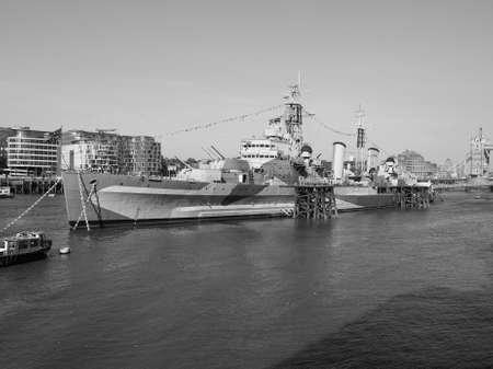 permanently: LONDON, UK - JUNE 11, 2015: HMS Belfast ship originally a Royal Navy light cruiser is now permanently moored on the River Thames as a museum ship in black and white Editorial
