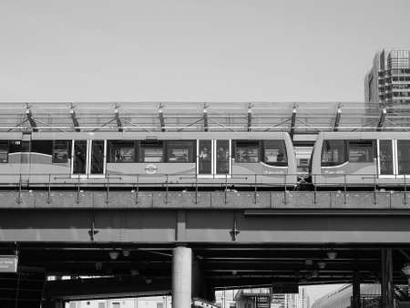 docklands: LONDON, UK - JUNE 11, 2015: The DLR meaning Docklands Light Railway links the docks redevelopment area in East London with the city centre in black and white Editorial