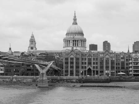 millennium bridge: LONDON, UK - JUNE 10, 2015: People crossing the Millennium Bridge linking the City of London with the South Bank between St Paul Cathedral and Tate Modern art gallery in black and white Editorial