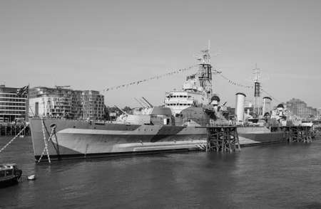 hms: LONDON, UK - JUNE 11, 2015: HMS Belfast ship originally a Royal Navy light cruiser is now permanently moored on the River Thames as a museum ship in black and white Editorial