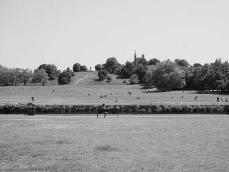 greenwich: LONDON, UK - JUNE 11, 2015: Visitors at Greenwich park on Royal Observatory hill in black and white