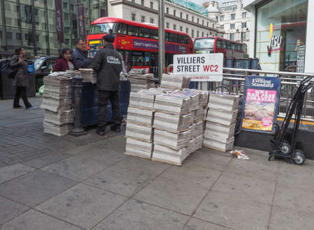 evening newspaper: LONDON, UK - JUNE 09, 2015: Distribution of the Evening Standard free newspaper on the Strand near Charing Cross station in black and white Editorial